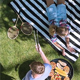 para odpoczywająca na trawniku obok rakietek do badmintona