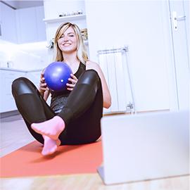 kobieta siedząca na macie z fit ball w rękach
